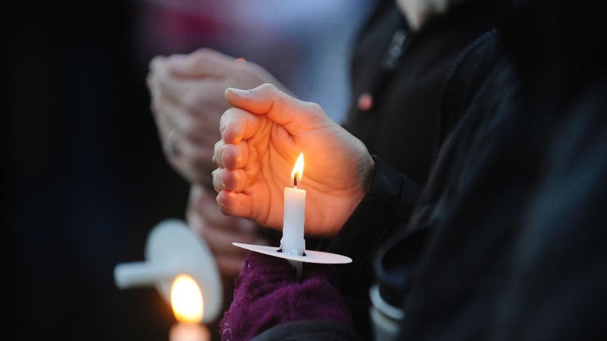 A mourner cradles a candle Monday, Oct. 10, 2016, during a vigil attended by about 1,000 at Harwood Union High School in Duxbury, Vt., held for the teenaged victims killed in Saturday night's crash on Interstate 89 in Williston. Four of the five teens killed by the wrong-way driver were students at Harwood. The fifth student killed was from Fayston and attended a private school in New Hampshire. (Stefan Hard/Times Argus via AP)