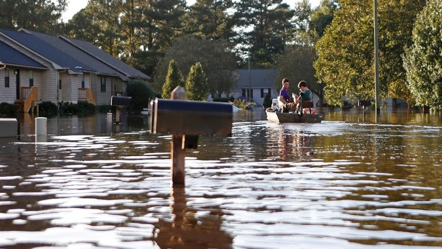 Kyle Hawley, right, and roommate Trey Wood, pilot their boat through the streets of their neighborhood, flooded by water associated with Hurricane Matthew, as they gather belongings from their home, Wednesday, Oct. 12, 2016, in Greenville, N.C. (AP Photo/Brian Blanco)