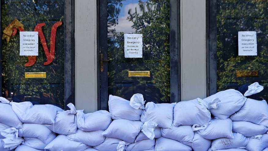 Sandbags and no entry signs are seen in front of apartments located near the Tar River as floodwaters associated with Hurricane Matthew continue to rise on Wednesday, Oct. 12, 2016, in Greenville, N.C. (AP Photo/Brian Blanco)