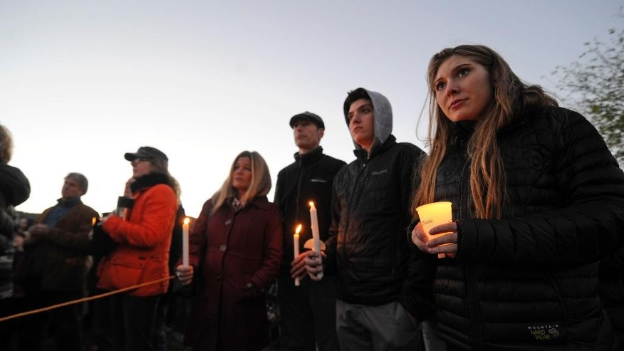 Mourners hold candles Monday, Oct. 10, 2016, during a vigil attended by about 1,000 at Harwood Union High School in Duxbury, Vt., held for the teenaged victims killed in Saturday night's crash on Interstate 89 in Williston. Four of the five teens killed by the wrong-way driver were students at Harwood. The fifth student killed was from Fayston and attended a private school in New Hampshire. (Stefan Hard/Times Argus via AP)
