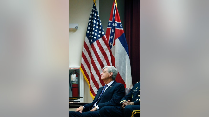 FILE -In this Thursday, Sept. 1, 2016 file photo, Gov. Phil Bryant sits under a flag display, with both the American flag and the Mississippi state flag, during a retirement ceremony for outgoing state Army and Air National Guard Adjutant Gen. Augustus Leon Collins at the Mississippi National Guard Joint Force headquarters auditorium in Jackson, Miss. An effort to erase the Confederate battle emblem from the Mississippi flag is failing because sponsors didn't gather enough signatures to put an initiative on the 2018 ballot. (AP Photo/Rogelio V. Solis, File)