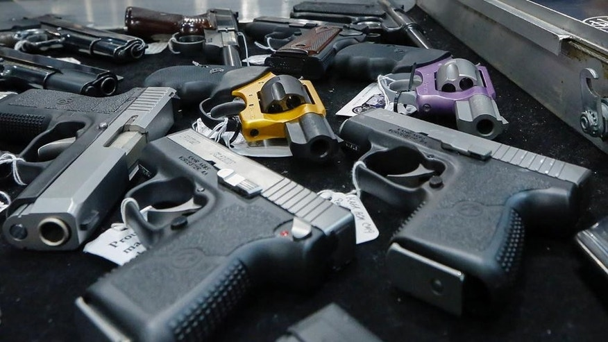 FILE - In this Saturday, Jan. 26, 2013 file photo, handguns are displayed on a vendor's table at an annual gun show in Albany, N.Y. In an Associated Press USA TODAY Network investigation into accidental shootings involving children from Jan. 1, 2014, to June 30, 2016, more than 320 minors and more than 30 adults were fatally shot. (AP Photo/Philip Kamrass)