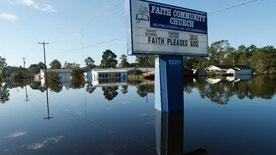 Floodwaters associated with Hurricane Matthew surround homes and a church sign Thursday, Oct. 13, 2016, in Lumberton, N.C.  Gov. Pat McCrory said Thursday the number of power outages was down to about 55,000, from a high of nearly 900,000 when the storm hit last week.  (AP Photo/Brian Blanco)