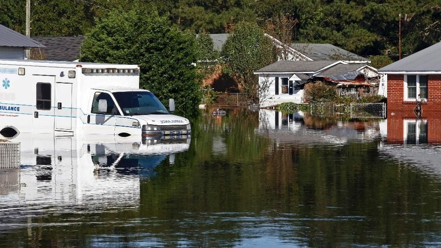 Floodwaters associated with Hurricane Matthew surround homes and an ambulance on Thursday, Oct. 13, 2016, in Lumberton, N.C.  Gov. Pat McCrory said Thursday the number of power outages was down to about 55,000, from a high of nearly 900,000 when the storm hit last week. (AP Photo/Brian Blanco)