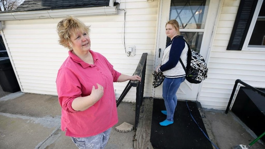 In this April 14, 2016 photo, Denise Kirchner and her daughter, Madison, right, talk about an accidental shooting a few days before Thanksgiving 2015, in their home in Toledo, Iowa. Madison and her older brother, Dylan, were cleaning guns when one accidentally discharged. A bullet passed through Madison's left breast, narrowly missing her spine but leaving six holes in her stomach and intestines. It then passed through Denise's thigh before ending up in a cupboard. (AP Photo/Charlie Neibergall)