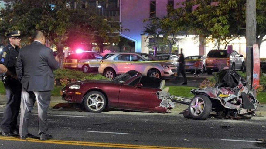 Police survey the wreckage of a Mazda Miata that was split in half after a collision with a Mercedes-Benz in Rockville Centre, on New York's Long Island.