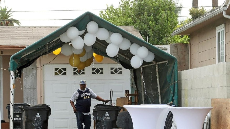 A man stands under a driveway canopy with party equipment and balloons Sunday, Oct. 16, 2016, at the scene of a shooting that left three people dead and 12 wounded early Saturday at a restaurant operating out of a converted home in a neighborhood west of downtown Los Angeles. Police said Sunday that detectives are still trying to determine a motive for the gunfire that erupted during a birthday celebration attended by more than 100 people. (AP Photo/Reed Saxon)