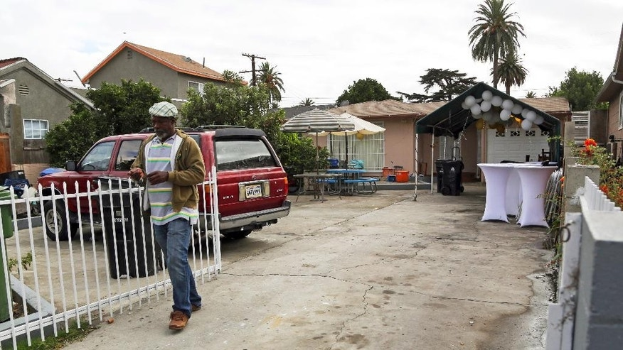 An unidentified man walks down the driveway Sunday, Oct. 16, 2016, at the scene of a shooting that left three people dead and 12 wounded early Saturday at a restaurant operating out of a converted home in a neighborhood west of downtown Los Angeles. Police said Sunday that detectives are still trying to determine a motive for the gunfire that erupted during a birthday celebration attended by more than 100 people. (AP Photo/Reed Saxon)
