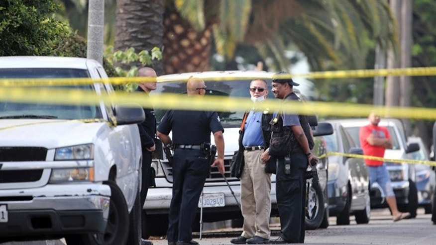 Los Angeles police investigators work the scene of a fatal shooting in the Crenshaw District neighborhood of Los Angeles, Saturday, Oct. 15, 2016.