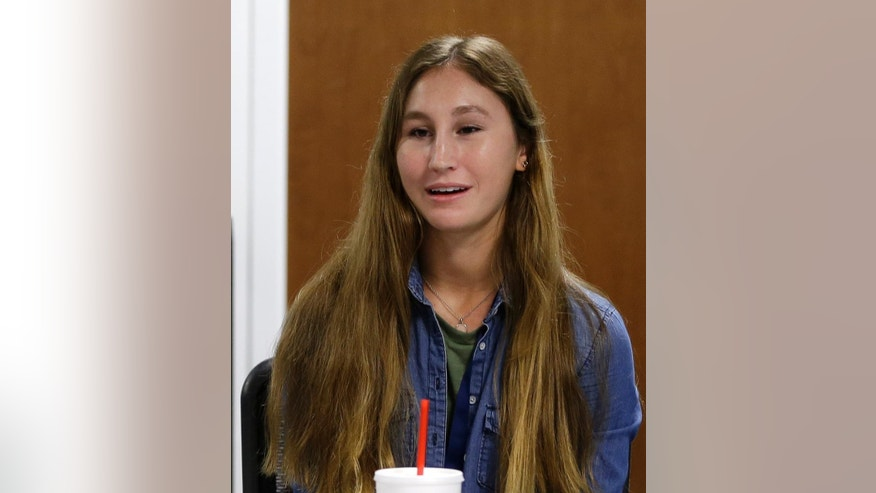 In this photo taken Wednesday, Sept. 7, student and author Paige Fries talks to a reporter at Florida Atlantic University High School, in Boca Raton, Fla. Fries recently published a science-fiction novel. At tuition-free Florida Atlantic University High School, all students can simultaneously earn their high school diploma and bachelor's degree. (AP Photo/Alan Diaz)