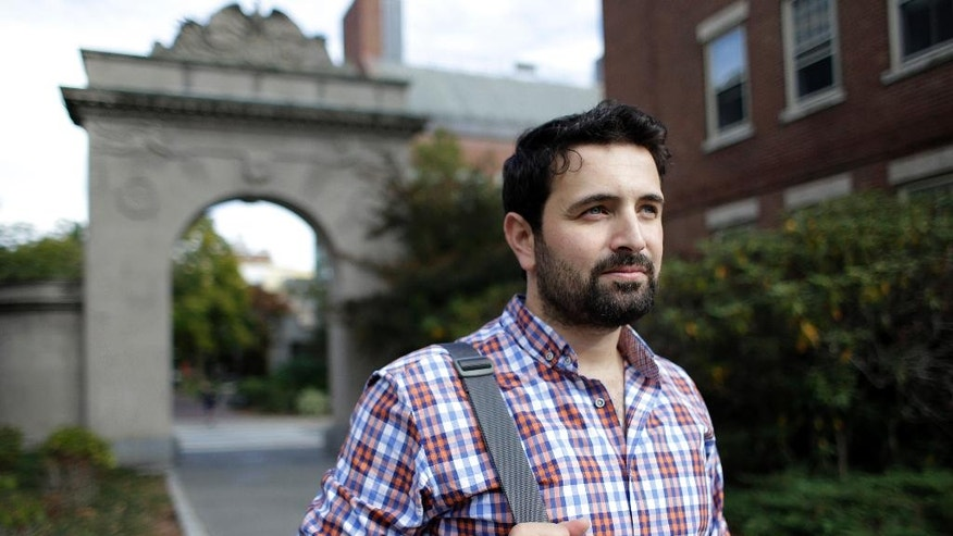 In this Thursday, Oct. 13, 2016 photo, Khaled Almilaji, who coordinated a campaign that vaccinated 1.4 million Syrian children and risked his life to provide medical care during the country's civil war, stands for a portrait on the campus of Brown University in Providence, R.I. Almilaji is now in the Ivy League, learning about how to rebuild Syria's health system when the war finally ends. (AP Photo/Steven Senne)