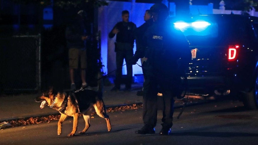 FILE - In this Oct. 12, 2016, file photo, police search for a suspect after two officers were shot in the East Boston neighborhood of Boston. Police said on Oct. 17, 2016, that the two officers have been upgraded to stable condition. (AP Photo/Charles Krupa, File)