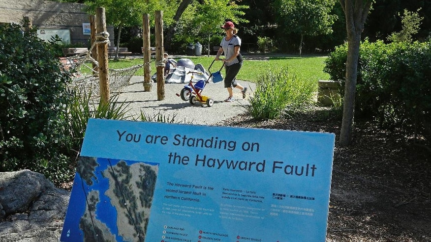 In this Tuesday, Oct. 18, 2016 photo, a sign notifying people they are standing on the Hayward Fault stands at the children's zoo area at the Oakland Zoo in Oakland, Calif. New research published in the journal Science Advances on Wednesday, Oct. 19, 2016 found that the Hayward Fault may be linked to another fault. (AP Photo/Ben Margot)