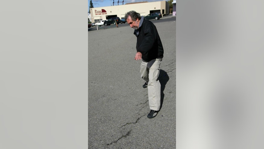 File - In this March 21, 2006, file photo, David Schwartz, geologist for the U.S. Geological Survey (USGS), walks along the Hayward Fault in a parking lot in Hayward, Calif. New research published in the journal Science Advances on Wednesday, Oct. 19, 2016, found that the Hayward Fault may be linked to another fault. (AP Photo/Jeff Chiu, File)