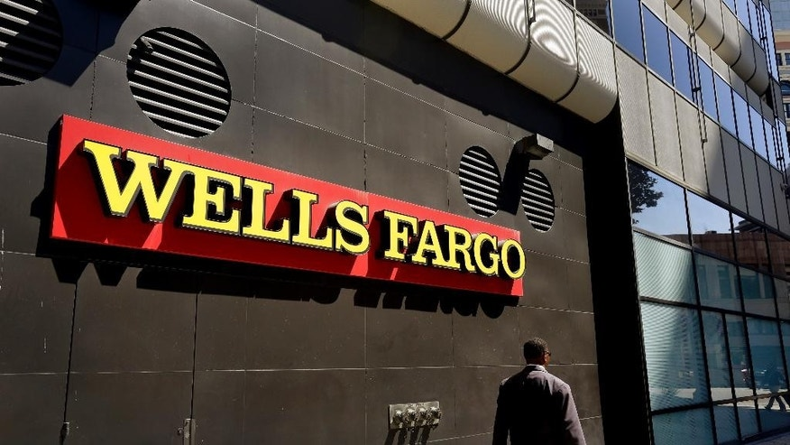 FILE - In this July 14, 2014 file photo, a man passes by a Wells Fargo bank in Oakland, Calif. California Attorney General Kamala Harris announced she has launched a criminal investigation into the sales practices of Wells Fargo, on Wednesday, Oct. 19, 2016. (AP Photo/Ben Margot, File)