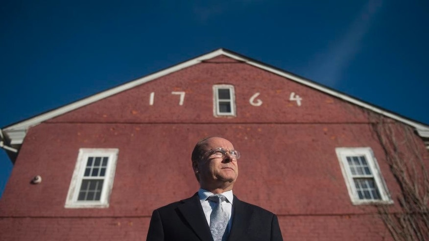In an Oct. 11, 2016 photo, Camden County Historical Society President Chris Perks stands in front of the historic Hugg-Harrison House in Bellmawr, NJ. Perks is part of an effort to save the Hugg-Harrison House. Federal officials are exploring ways to avoid razing a historic Revolutionary War-era home in New Jersey as part of a $900 million interchange reconstruction project. (Chris LaChall/The Courier-Post via AP)