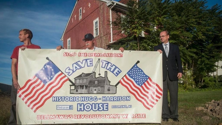 In an Oct. 11, 2016 photo, from the left; Camden County Historical Society member Adin Mickle, Rev. Vincent Kovlak of Bellmawr Baptist Church, and Camden County Historical Society President Chris Perks hold a banner supporting the effort to save the historic Hugg-Harrison House in Bellmawr, NJ. Federal officials are exploring ways to avoid razing a historic Revolutionary War-era home in New Jersey as part of a $900 million interchange reconstruction project. (Chris LaChall/The Courier-Post via AP)