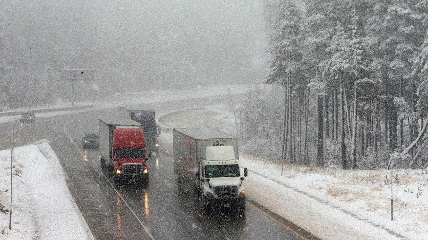 Vehicles drive through fog and light snow on westbound Interstate 80 on Monday, Oct. 17, 2016, near Soda Springs, Calif. A weekend storm brought rain to Northern California and snow to the Sierra Nevada. (AP Photo/Rich Pedroncelli)