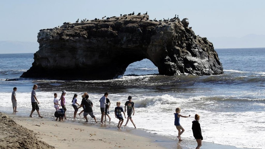 Beach goers wade in the surf at Natural Bridges State Beach Wednesday, Oct. 19, 2016, in Santa Cruz, Calif. Santa Ana winds gusted out of the mountains of Southern California on Wednesday, driving up temperatures and raising the danger of wildfires in the drought-stricken region. Much of the rest of the state, including the San Francisco Bay Area and the Central Valley, was also expected to have above-normal temperatures, although no red flag warnings were posted in those regions. (AP Photo/Marcio Jose Sanchez)