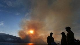 ** HOLD FOR OVERNIGHT MOVEMENT ** File - In this Aug. 26, 2016 file photo, firefighters just in from Pennsylvania get briefed a wildfire as it burns off the shore of Jackson Lake in Grand Teton National Park, Wyo. With measureable snowfall already in parts of the Rockies and Northwest, the 2016 wildfire season is pretty much over in much of the West. Snow fell this last week in Washington, Oregon, Montana and Wyoming. About a foot of snow fell in areas of western Wyoming in elevations as low as 7,000 feet. Snow on Monday covered Old Faithful in Yellowstone National Park, where wildfires were active this summer. (AP Photo/Brennan Linsley, File)