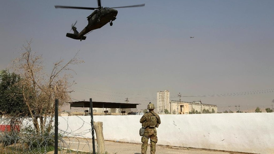A U.S. Army soldier watches a helicopter belonging to the international coalition forces land on a base outside Mosul, Iraq, Wednesday, Oct. 19, 2016. The U.S. has just as much to gain from the operation to recapture Mosul as the Iraqis themselves. Since 2014, the U.S. has provided airstrikes and advise-and-assist operations to put the beleaguered Iraqi military back on its feet after the Islamic State group gutted it of weapons, supplies and soldiers during its blitzkrieg across Iraq and Syria. (AP Photo)