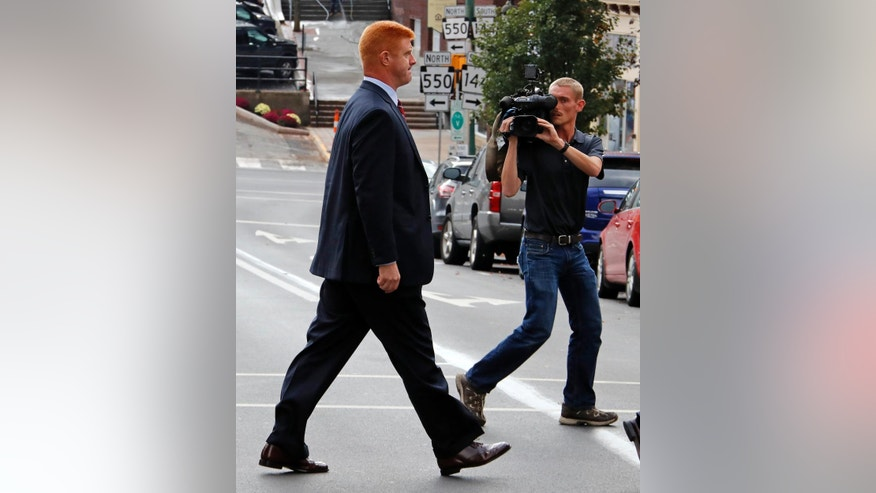 Former Penn State University assistant football coach Mike McQueary, left, leaves the Centre County Courthouse Annex for lunch in Bellefonte, Pa., Monday, Oct. 17, 2016. A civil trial that's set to begin will determine if Penn State should pay for a claim it mistreated the former assistant coach who provided key evidence used to convict child molester Jerry Sandusky. (AP Photo/Gene J. Puskar)
