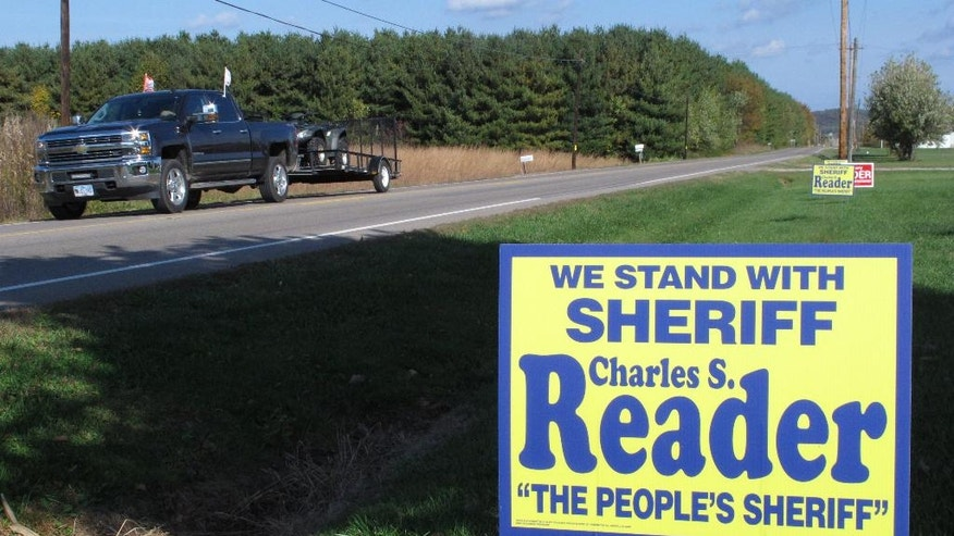 In this Tuesday, Oct. 18, 2016 photo, a truck passes a sign for the election of Pike County Sheriff Charles Reader in Waverly, Ohio. The still-unsolved killing of eight members of the Rhoden family, an investigation overseen by Reader and the Ohio Attorney General's Office, has become an election issue for many voters in the rural southern Ohio county. (AP Photo/Andrew Welsh-Huggins)