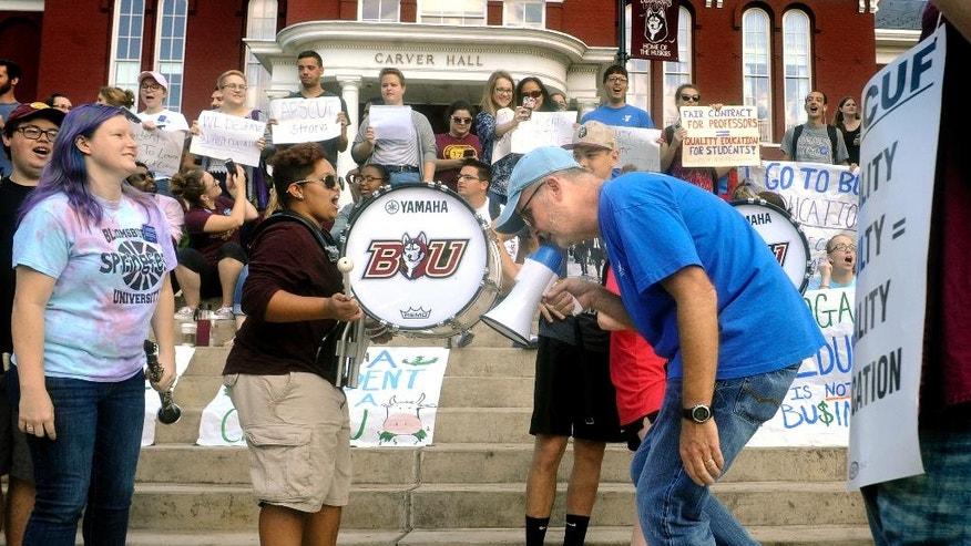 Bloomsburg University history Professor Bill Hudon leads a chant with a bullhorn while stepping to the beat of drummers during picketing with fellow faculty members in front of Carver Hall on campus in Bloomsburg, Pa., Wednesday, Oct. 19, 2016. Behind him students rally in support of the striking faculty. Professors at multiple Pennsylvania state universities went on strike Wednesday, disrupting classes midsemester for more than 100,000 students after contract negotiations hit an impasse. (Bill Hughes/Bloomsburg Press Enterprise via AP)