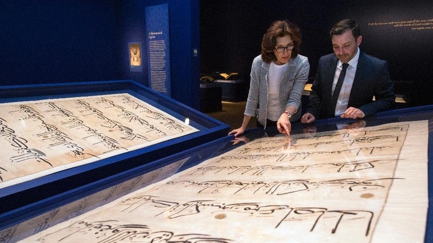 "In this photo taken Oct. 20, 2016, Massumeh Farhad, left, and Simon Rettig, curators of the exhibit ""The Art of the Qur'an: Treasures from the Museum of Turkish and Islamic Arts,"" look at pages from a 5-foot by 7-foot Quran displayed as part of the exhibit at the Sackler Gallery in Washington. (AP Photo/Molly Riley)"