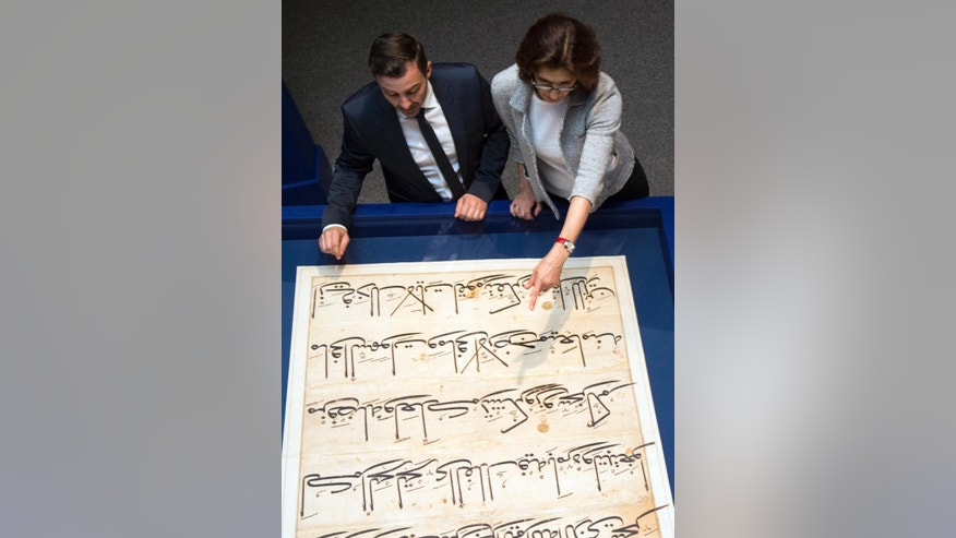"In this photo taken Oct. 20, 2016, Simon Rettig, left, and Massumeh Farhad, curators of the exhibit ""The Art of the Qur'an: Treasures from the Museum of Turkish and Islamic Arts,"" look at pages from a 5-foot by 7-foot Quran displayed as part of the exhibit at the Sackler Gallery in Washington. (AP Photo/Molly Riley)"