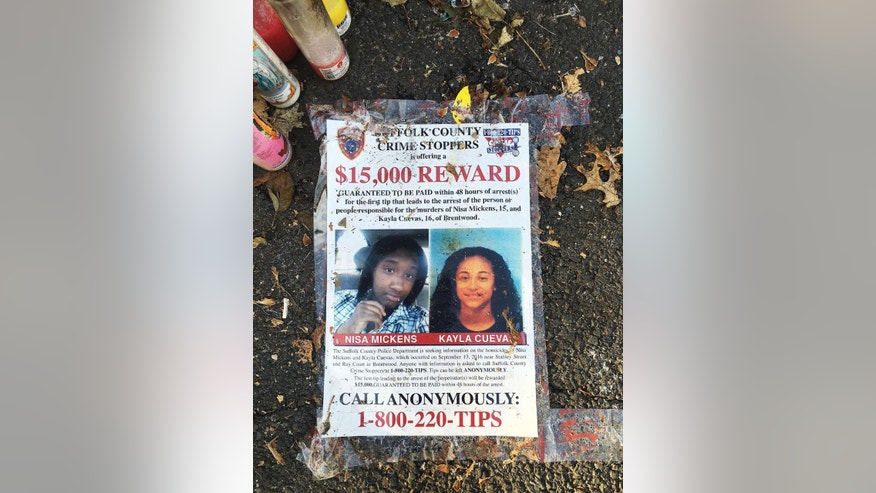 FILE- In this Sept. 27, 2016 file photo, a poster featuring photos of Nisa Mickens and Kayla Cueva is part of a memorial near the spot where their bodies were found in Brentwood, N.Y. The girls are among four teenagers from Brentwood High School that have been found dead this past month in a string of brutal killings that assistant Suffolk County Police Commissioner Justin Meyers says may be tied to gang violence. (AP Photo/Claudia Torrens, File)
