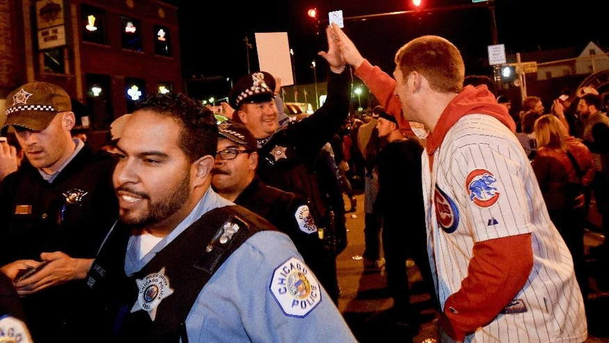 A Chicago Cubs fan high-fives a Chicago police officer outside Wrigley Field after the Cubs defeated the Los Angeles Dodgers 5-0 in Game 6 of baseball's National League Championship Series, Saturday, Oct. 22, 2016, in Chicago. The Cubs advanced to the World Series. (AP Photo/Matt Marton)