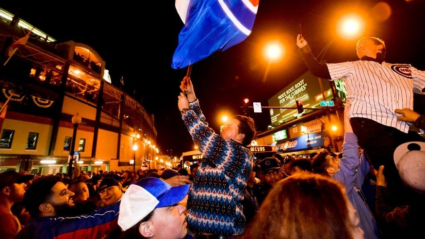 Chicago Cubs fans celebrate outside Wrigley Field after the Cubs defeated the Los Angeles Dodgers 5-0 in Game 6 of baseball's National League Championship Series, Saturday, Oct. 22, 2016, in Chicago. The Cubs advanced to the World Series. (AP Photo/Matt Marton)