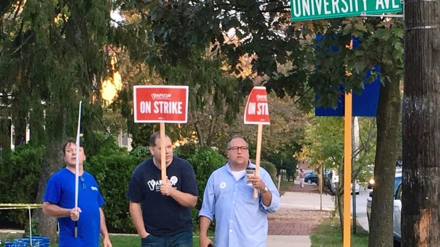 Picketers standing with signs near West Chester University on Oct. 19.
