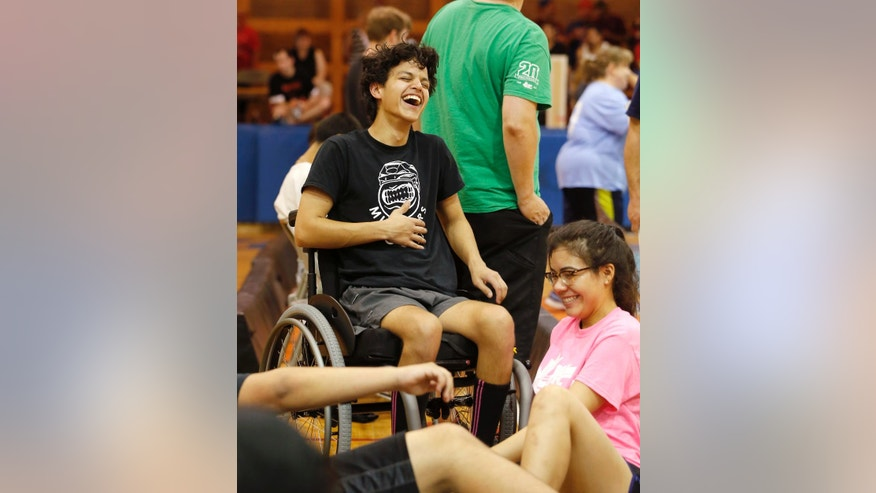 "In this Sunday, June 12, 2016 photo, Jonathan Annicks, left, laughs with his girlfriend, Cynthia Valentin, during an indoor field hockey game in Berwyn, Ill. The April shooting which paralyzed him from the chest down, inevitably, changed their relationship. ""At first it was hard,"" he says. ""She was distraught and I was lost ... But eventually we worked it out."" (AP Photo/Charles Rex Arbogast)"
