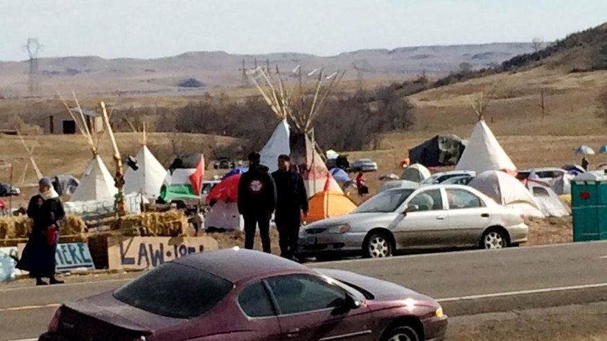 Teepees and numerous tents are set up Monday, Oct. 24, 2016, by Dakota Access oil pipeline protesters in southern North Dakota on property owned by the pipeline company. Protesters say they have treaty rights to the land from the 1800s. (AP Photo/Blake Nicholson)
