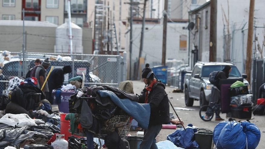 File - In this March 8, 2016, file photograph, homeless people clear their belongings from a camp, as city officials warned that the homeless had to move from their makeshift structures along the sidewalks in the area, near the Denver Rescue Mission in downtown Denver. A lawsuit challenging Denver's sweeps of the homeless is the latest in a string of cases opposing crackdowns on people camping in public around the country. (AP Photo/David Zalubowski, File)