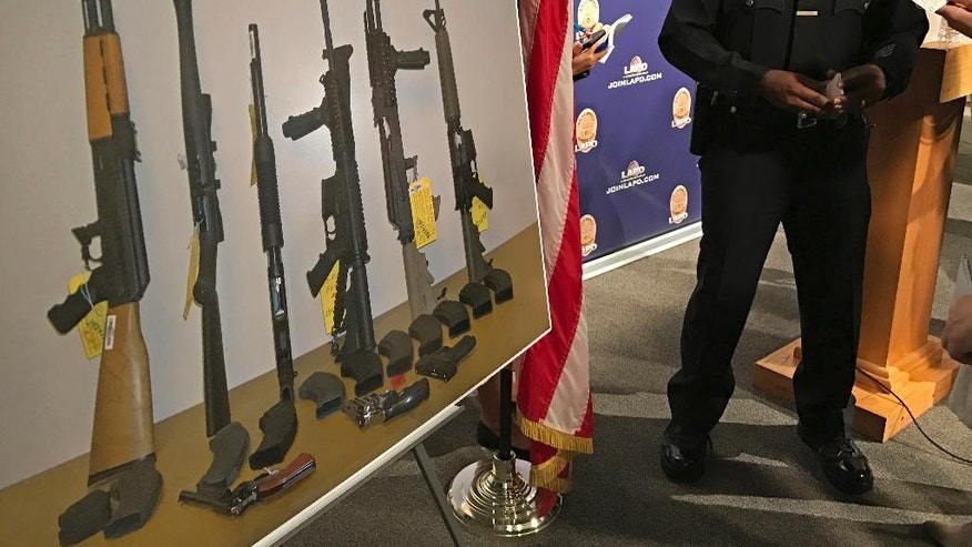 Los Angeles Police Cmdr. Horace Frank, right, shows a photo of multiple weapons found in the home of a man charged with making terrorist threats to the Islamic Center of Southern California, during a police news conference Tuesday, Oct. 25, 2016 in Los Angeles. Mark Lucian Feigin was arrested last week on the charge, which has been designated as a hate crime, according to authorities. Feigin, 40, has been released on bail. Police say Feigin first called the Islamic center Sept. 19 and left a hate-filled voicemail. The next day, they say, he called and threatened to kill people at the center. (AP Photo/Damian Dovarganes)
