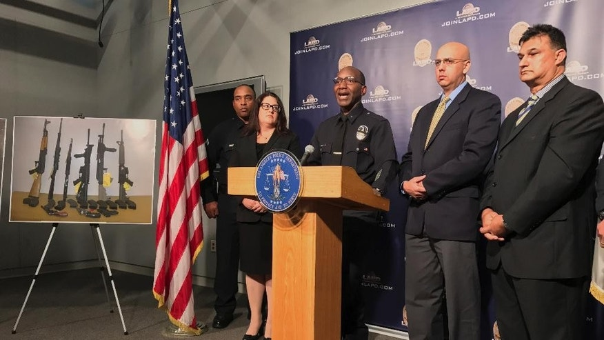 Los Angeles Police Cmdr. Horace Frank, third from left, is joined by Omar Ricci, Spokesperson Islamic Center of Southern California, second from right, and Mahomed Akbar Khan, far right, as police shows a photo of multiple weapons found in the home of a man charged with making terrorist threats to the Islamic Center of Southern California, during a police news conference Tuesday, Oct. 25, 2016 in Los Angeles. Mark Lucian Feigin was arrested last week on the charge, which has been designated as a hate crime, according to authorities. Feigin, 40, has been released on bail. Police say Feigin first called the Islamic center Sept. 19 and left a hate-filled voicemail. The next day, they say, he called and threatened to kill people at the center. (AP Photo/Damian Dovarganes)