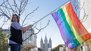 "FILE - In this Nov. 14, 2015, file photo, Sandy Newcomb poses for a photograph with a rainbow flag as Mormons gather for a mass resignation from the Church of Jesus Christ of Latter-day Saints, in Salt Lake City. Mormon leaders are telling gay and lesbian church members that attraction to people of the same sex is not a sin or a measure of their faithfulness. But they are reminding those members that acting on those feelings by having sex violates fundamental doctrinal beliefs that won't change. The message is part of the Mormon church's ""Mormon and Gay"" website launched Tuesday, Oct. 25, 2016, with dozens of articles, teachings, videos and stories from Mormons who identify themselves as gay. (AP Photo/Rick Bowmer, File)"