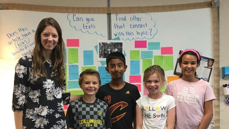 In this photo provided by Kate Baker, taken Oct. 19, 2016, Fourth grade teacher Halie Miller and students at Glacier Ridge Elementary School in Dublin, Ohio are using the election as a teaching tool for her students in social studies and math. From left are, Halie Miller, Calvin McCormick, Sriram Katta, Audrey DiCesare and Mia Dahi. (Kate Baker via AP)