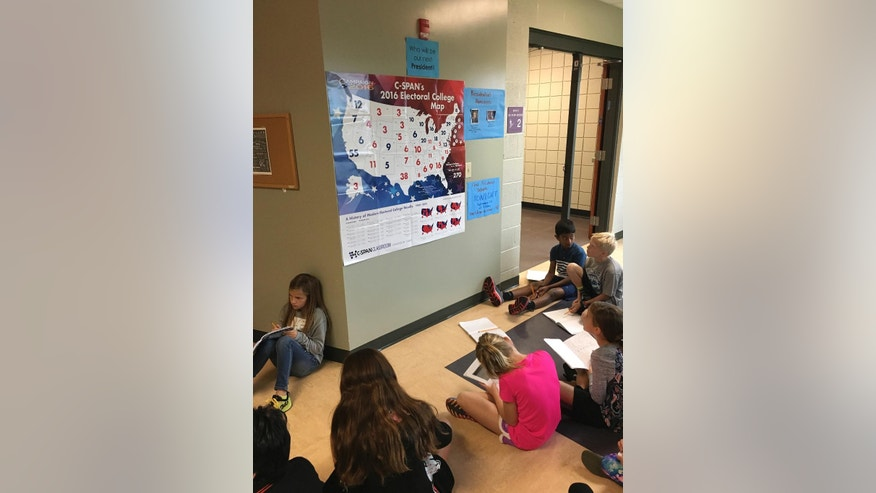 In this photo provided by Halie Miller, taken Sept. 26, 2016, students in Halie Miller's fourth grade class at Glacier Ridge Elementary School in Dublin, Ohio, use an Electoral College map to create different combinations of numbers to get to the magic number of 270 electoral votes needed for victory as part of a math assignment. (Halie Miller via AP)