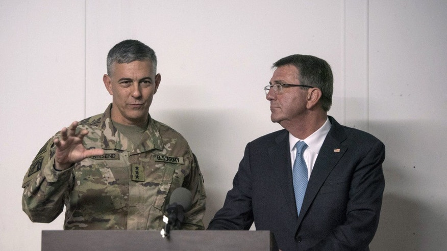 In this photo provided by the Defense Department, taken Oct. 23, 2016, Defense Secretary Ash Carter listens as U.S. Army Lt. Gen. Stephen Townsend, commander of Combined Joint Task Force-Operation Inherent Resolve, speaks during a news conference in Erbil, Iraq. Townsend, the commander of the U.S.-led coalition against the Islamic State group says there's an urgent need to encircle the extremists' stronghold in the Syrian city of Raqqa because of intelligence warnings that attacks on Western targets are being plotted there. (U.S. Air Force Tech. Sgt. Brigitte N. Brantley/DoD via AP)