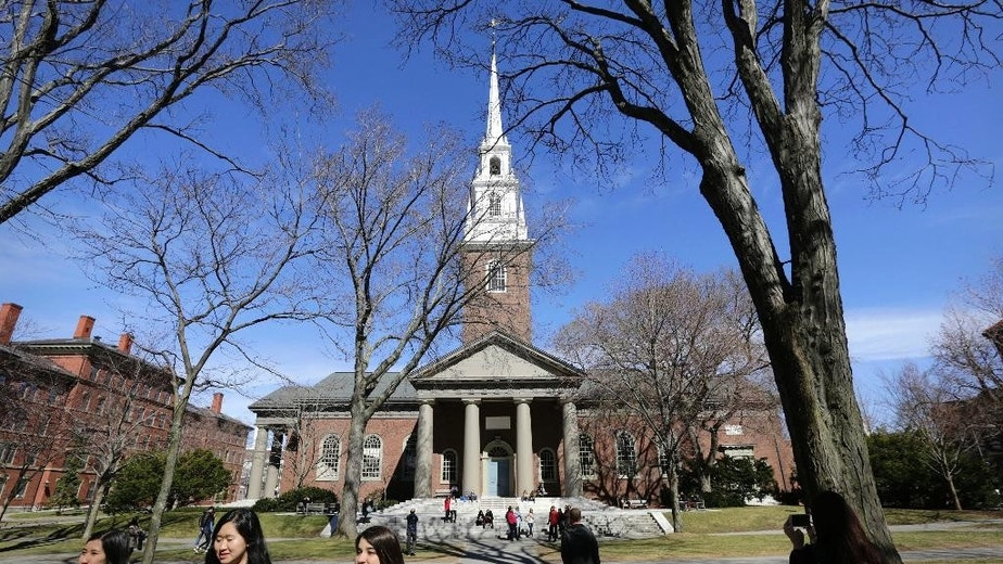 FILE - In this March 13, 2016, file photo, people walk near Memorial Church on the campus of Harvard University in Cambridge, Mass. The university's first female president, Drew Faust, announced Friday, May 6, 2016, that students who join Harvard's male-only social clubs won't be able to serve as sports captains or leaders of other campus groups starting in fall 2017. (AP Photo/Steven Senne, File)