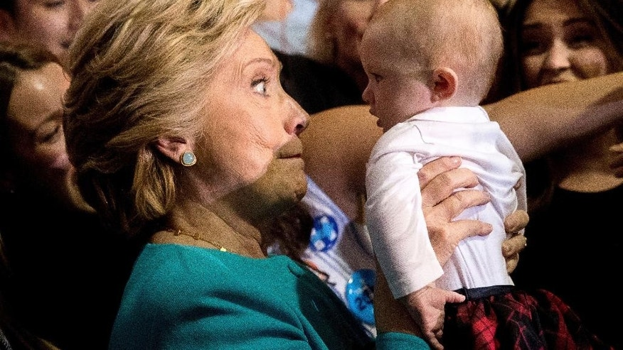Democratic presidential candidate Hillary Clinton holds up a baby as she greets members of the audience after speaking at a rally at Palm Beach State College in Lake Worth, Fla., Wednesday, Oct. 26, 2016. (AP Photo/Andrew Harnik)