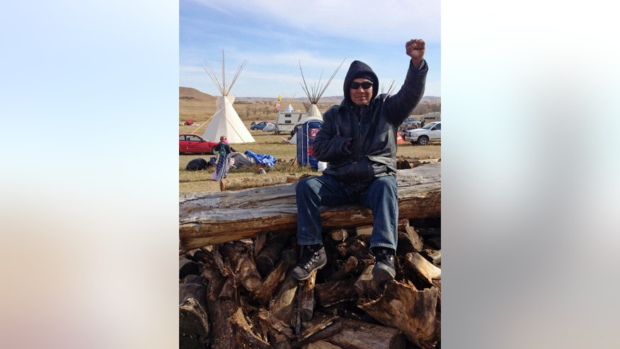 Loren Bagola, from the Cheyenne River Reservation in South Dakota, helps handle security Monday, Oct. 24, 2016, at the Dakota Access oil pipeline protest in southern North Dakota. Bagola is sitting atop a pile of logs that protesters prepared to use to block a highway. The long-running dispute over the Dakota Access oil pipeline expanded to private land recently purchased by the pipeline builders, with protesters who say the area rightfully belongs to Native Americans setting up camp and vowing to stay put until the project is stopped.  (AP Photo/Blake Nicholson)