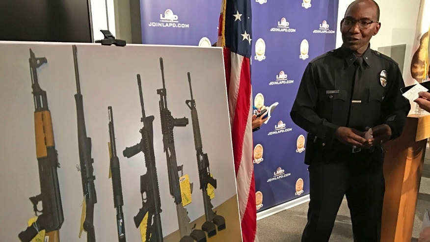 Los Angeles Police Cmdr. Horace Frank, right, shows a photo of multiple weapons found in the home of a man charged with making terrorist threats to the Islamic Center of Southern California, during a police news conference Tuesday, Oct. 25, 2016 in Los Angeles.