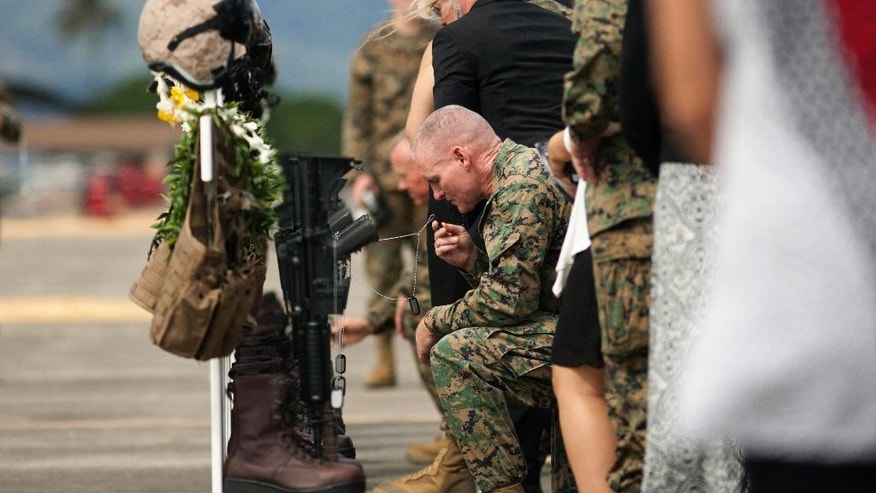 FILE - This Jan. 22, 2016 file photo shows family, friends and comrades paying their respects during a memorial service at Marine Corps Base Hawaii in Kaneohe Bay, Hawaii for the 12 U.S. Marines who died when their helicopters crashed off the North Shore of Oahu. The Marine Corps is blaming pilot error and other factors for the nighttime collision of two helicopters that killed 12 Marines off the coast of Hawaii, Tuesday, Oct. 25, 2016. (AP Photo/Caleb Jones, File)