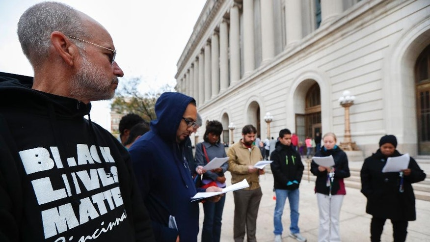 Demonstrators gather to pray for justice and reconciliation outside Hamilton County Courthouse ahead of the trial against former University of Cincinnati police officer Ray Tensing, who shot and killed motorist Sam DuBose during a traffic stop, Tuesday, Oct. 25, 2016, in Cincinnati. The planned start of jury selection began Tuesday. Tensing faces charges of murder and voluntary manslaughter. (AP Photo/John Minchillo)