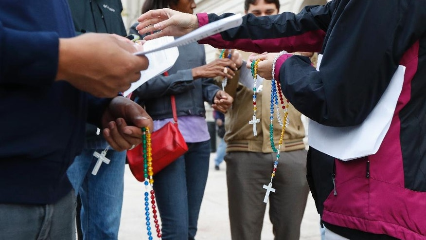 Demonstrators are handed rosary beads as they gather to pray for justice and reconciliation outside Hamilton County Courthouse ahead of the trial against former University of Cincinnati police officer Ray Tensing, who shot and killed motorist Sam DuBose during a traffic stop, Tuesday, Oct. 25, 2016, in Cincinnati. The planned start of jury selection began Tuesday. Tensing faces charges of murder and voluntary manslaughter. (AP Photo/John Minchillo)